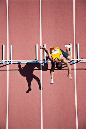 Runner jumping hurdles on track Stock Photo - Premium Royalty-Free, Code: 635-03515700
