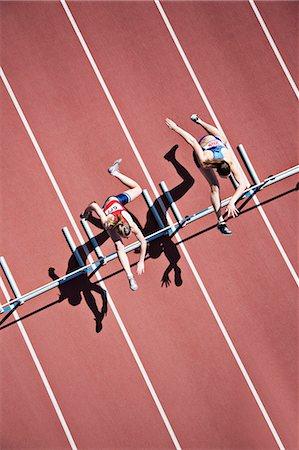 Runners jumping hurdles on track Stock Photo - Premium Royalty-Free, Code: 635-03515701