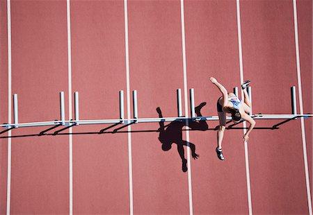 Runner jumping hurdles on track Stock Photo - Premium Royalty-Free, Code: 635-03515702