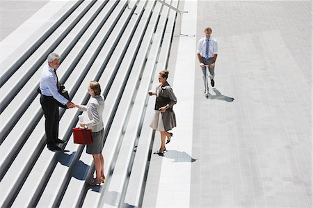 Business people shaking hands on stairs Stock Photo - Premium Royalty-Free, Code: 635-03515784