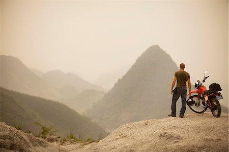 extremism - Man next to motorcycle viewing mountains Stock Photo - Premium Royalty-Free, Code: 635-03515809