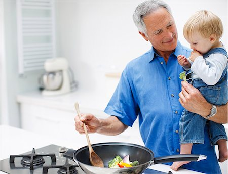 stove - Grandfather holding grandson and cooking Stock Photo - Premium Royalty-Free, Code: 635-03515908