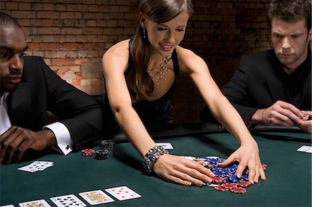 Woman gathering poker chips in casino Stock Photo - Premium Royalty-Free, Code: 635-03515949