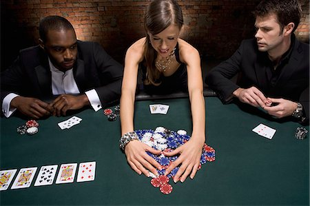 Woman gathering poker chips in casino Stock Photo - Premium Royalty-Free, Code: 635-03515950
