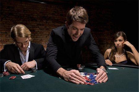 Man gathering poker chips in casino Stock Photo - Premium Royalty-Free, Code: 635-03515953