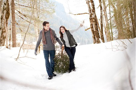 Couple pulling Christmas tree in woods Stock Photo - Premium Royalty-Free, Code: 635-03516010
