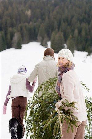 Family carrying Christmas tree through snow Stock Photo - Premium Royalty-Free, Code: 635-03516088