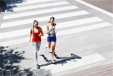 Friends running across urban crosswalk Stock Photo - Premium Royalty-Free, Code: 635-03516166