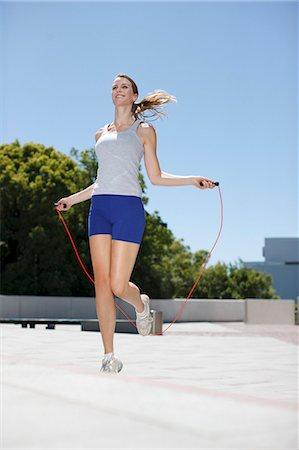 Woman skipping rope in urban plaza Stock Photo - Premium Royalty-Free, Code: 635-03516190