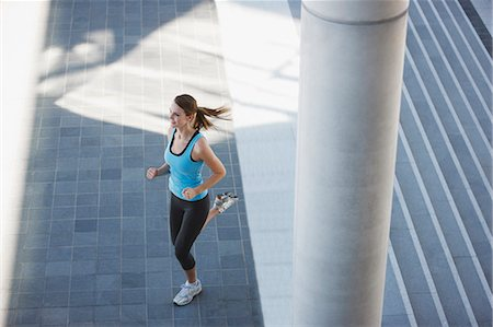 Woman running through urban setting Stock Photo - Premium Royalty-Free, Code: 635-03516206