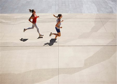 Friends running along urban sidewalk Stock Photo - Premium Royalty-Free, Code: 635-03516208