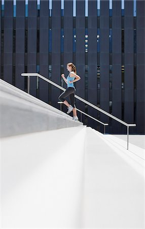 Woman running up urban staircase Stock Photo - Premium Royalty-Free, Code: 635-03516201