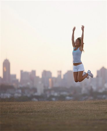 Woman jumping in urban park Stock Photo - Premium Royalty-Free, Code: 635-03516242