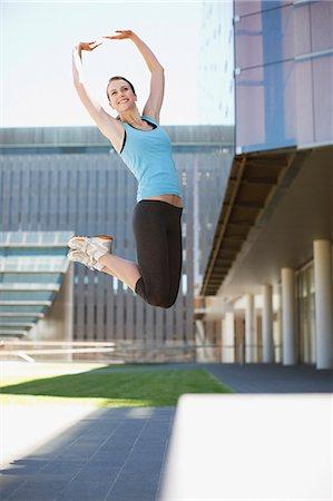 Woman jumping in urban setting Stock Photo - Premium Royalty-Free, Code: 635-03516243
