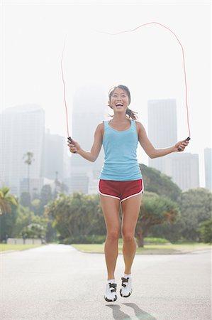 Woman skipping rope in urban park Stock Photo - Premium Royalty-Free, Code: 635-03516300