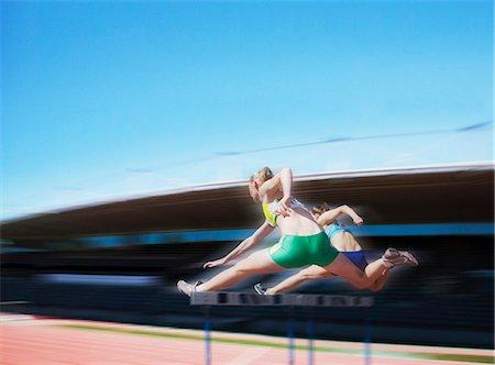 Runners jumping over hurdles Stock Photo - Premium Royalty-Free, Code: 635-03516322