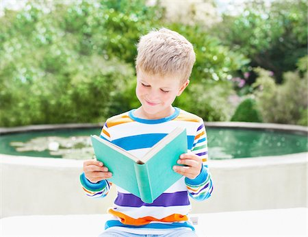Boy reading book near pond Stock Photo - Premium Royalty-Free, Code: 635-03577396