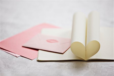 Close up of lipstick kiss on envelope and pages of notebook forming heart-shape Stock Photo - Premium Royalty-Free, Code: 635-03577441