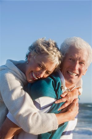 Smiling senior couple hugging on beach Stock Photo - Premium Royalty-Free, Code: 635-03577790