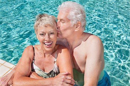 Senior man kissing wife in swimming pool Stock Photo - Premium Royalty-Free, Code: 635-03577834