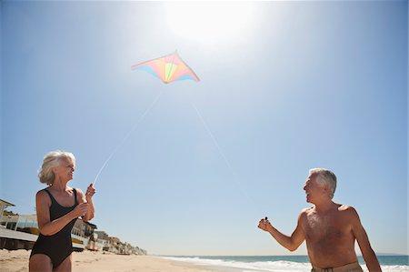 Senior couple flying kite on beach Stock Photo - Premium Royalty-Free, Code: 635-03577847