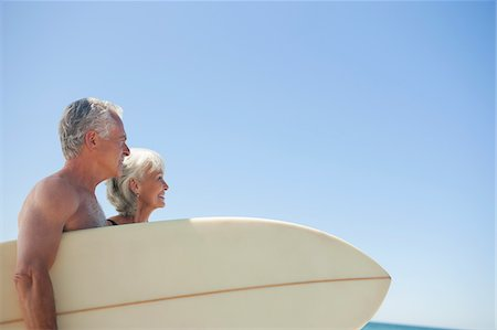 Senior couple with surfboard against blue sky Stock Photo - Premium Royalty-Free, Code: 635-03577843
