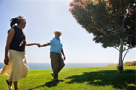 Senior couple holding hands on grass near ocean Stock Photo - Premium Royalty-Free, Code: 635-03577857