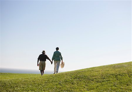 Senior couple holding hands on grassy hill Stock Photo - Premium Royalty-Free, Code: 635-03577859