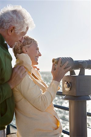 Smiling senior couple using coin-operated binoculars Stock Photo - Premium Royalty-Free, Code: 635-03577860