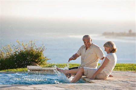 Senior couple splashing feet in swimming pool overlooking ocean Stock Photo - Premium Royalty-Free, Code: 635-03577877