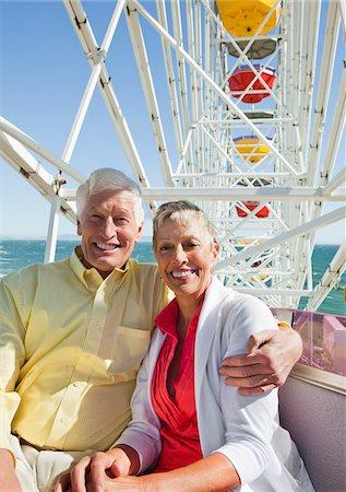 Smiling senior couple on ferris wheel at amusement park Stock Photo - Premium Royalty-Free, Code: 635-03577896