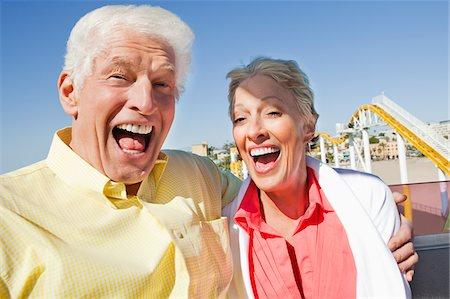 Enthusiastic senior couple on amusement park ride Stock Photo - Premium Royalty-Free, Code: 635-03577897