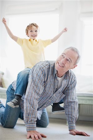 Grandfather crawling with grandson on back Stock Photo - Premium Royalty-Free, Code: 635-03577997