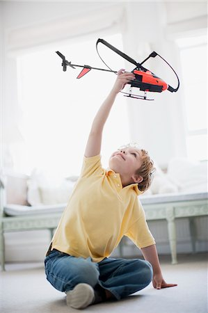 Boy playing with toy helicopter Stock Photo - Premium Royalty-Free, Code: 635-03577998