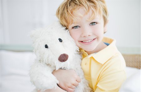 Smiling boy hugging teddy bear Stock Photo - Premium Royalty-Free, Code: 635-03578066