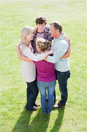 Smiling family hugging in a circle on grass Stock Photo - Premium Royalty-Free, Code: 635-03578101
