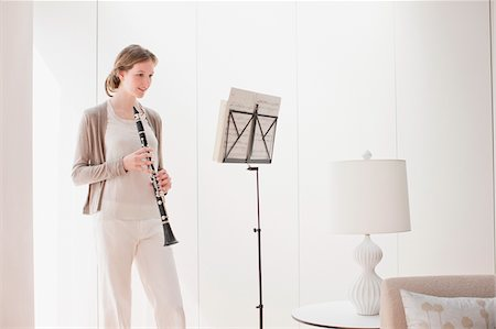 Woman holding clarinet and looking at sheet music Stock Photo - Premium Royalty-Free, Code: 635-03641416
