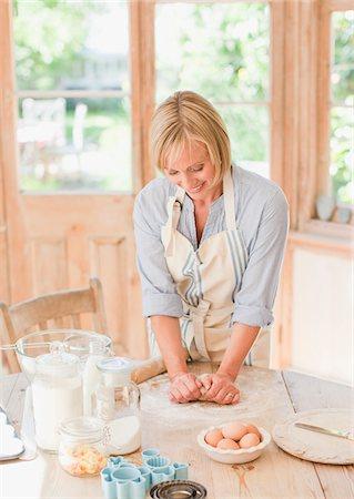 Smiling woman kneading dough on kitchen table Stock Photo - Premium Royalty-Free, Code: 635-03641421