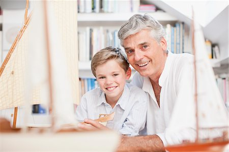 Smiling grandfather and grandson with model sailboats Stock Photo - Premium Royalty-Free, Code: 635-03641458
