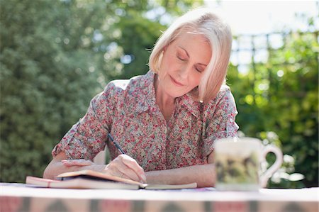Woman writing in journal at patio table Stock Photo - Premium Royalty-Free, Code: 635-03641481