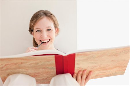 Smiling woman with sketch pad biting end of drawing pencil Stock Photo - Premium Royalty-Free, Code: 635-03641499