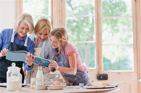Multi-generation females looking at cookbook and baking in kitchen Stock Photo - Premium Royalty-Free, Code: 635-03641491