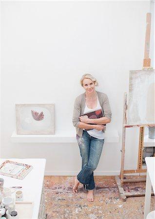 Smiling woman standing in art studio Stock Photo - Premium Royalty-Free, Code: 635-03641508