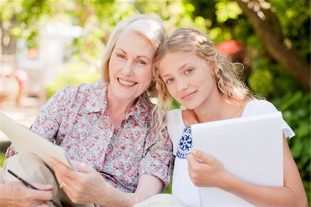 Grandmother and granddaughter holding sketch pads outdoors Stock Photo - Premium Royalty-Free, Code: 635-03641519