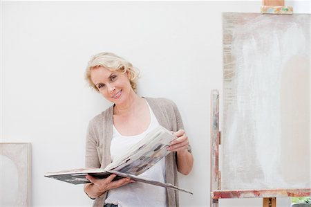 Smiling woman looking through book next to canvas in art studio Stock Photo - Premium Royalty-Free, Code: 635-03641535