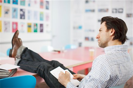 Businessman writing on notepad with feet up in office Stock Photo - Premium Royalty-Free, Code: 635-03641580