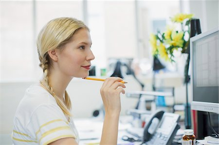 Businesswoman holding pencil and looking at computer monitor Stock Photo - Premium Royalty-Free, Code: 635-03641598