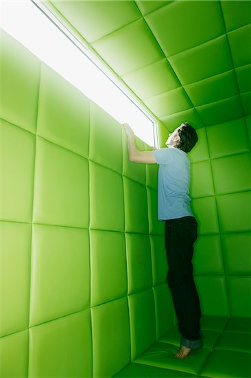 Man reaching to look out window in padded room Stock Photo - Premium Royalty-Free, Image code: 635-03641659