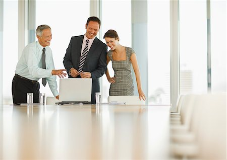 Smiling business people looking at laptop in conference room Stock Photo - Premium Royalty-Free, Code: 635-03641958
