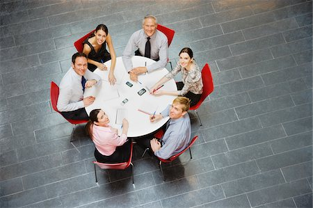 Smiling business people sitting at round table and having a meeting Stock Photo - Premium Royalty-Free, Code: 635-03641960